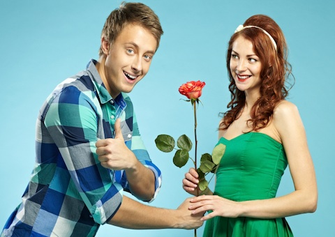 Young man giving a rose to his girlfriend, looking at camera and showing thumb